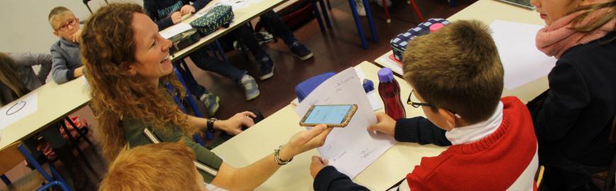 Une enseignante en classe qui enregistre un élève avec un GSM.  PROF/FWB